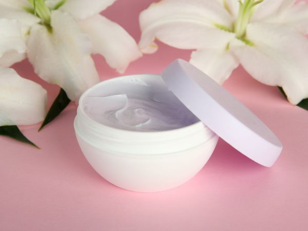 18086431 – cosmetic cream and beautiful lily, on pink background